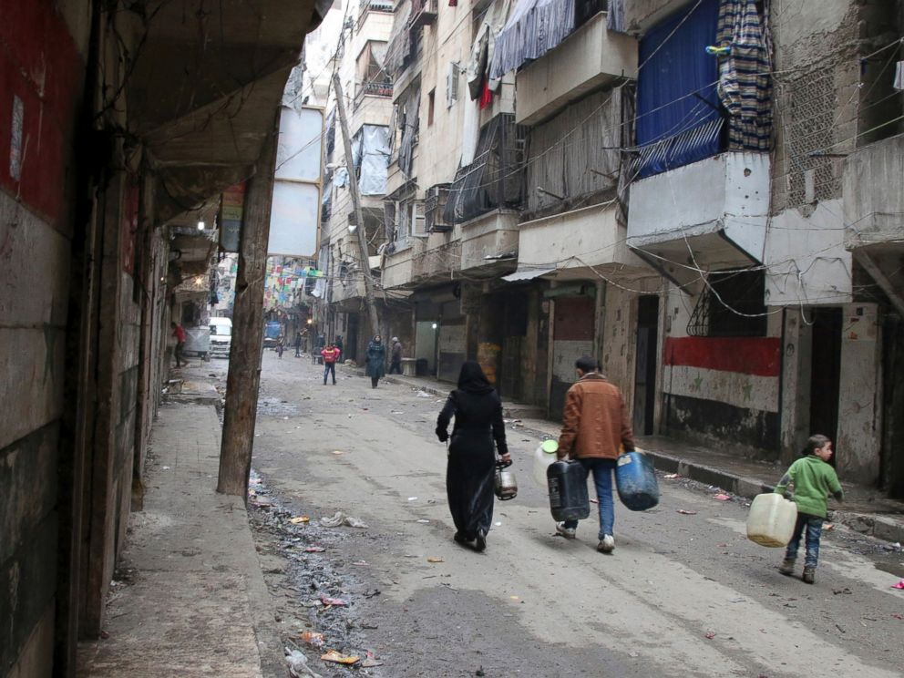 PHOTO: Civilians walk with containers for fuel and water in Aleppo, Syria.