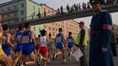 PHOTO: Runners pass under a pedestrian bridge in central Pyongyang