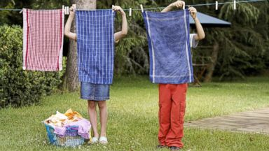 PHOTO: A boy and a girl hang laundry.