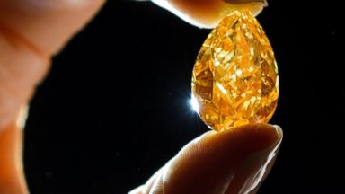 "PHOTO: ""The Orange"" a 14.82-carat pear-shaped, vivid orange diamond is seen here, Oct. 31, 2013 in Geneva."
