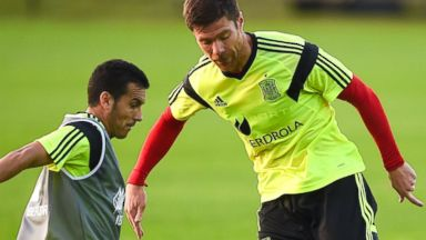 PHOTO: Pedro Rodriguez of Spain competes for the ball with his teammate, Xabi Alonso, during a Spain training session at the Centro de Entrenamiento do Caju, June 9, 2014, in Curitiba, Brazil.