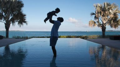 PHOTO: JAY Z stands in an infinity pool as he holds his daughter Blue Ivy Carter