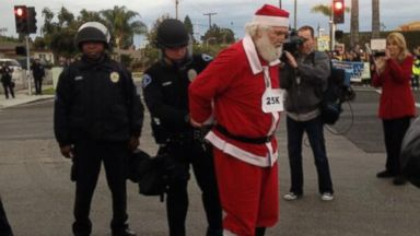 "PHOTO: Warehouse Workers @wwunited posted this photo to Twitter on Nov. 29, 2013, with the caption, ""Santa arrested @Walmart: Even Santas elves are paid a living wage. #walmartstrikers"""