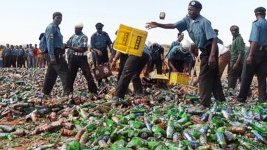 PHOTO: Sharia enforcers called Hisbah destroy thousands of bottles of beer outside northern Nigerias largest city of Kano on November 27, 2013.