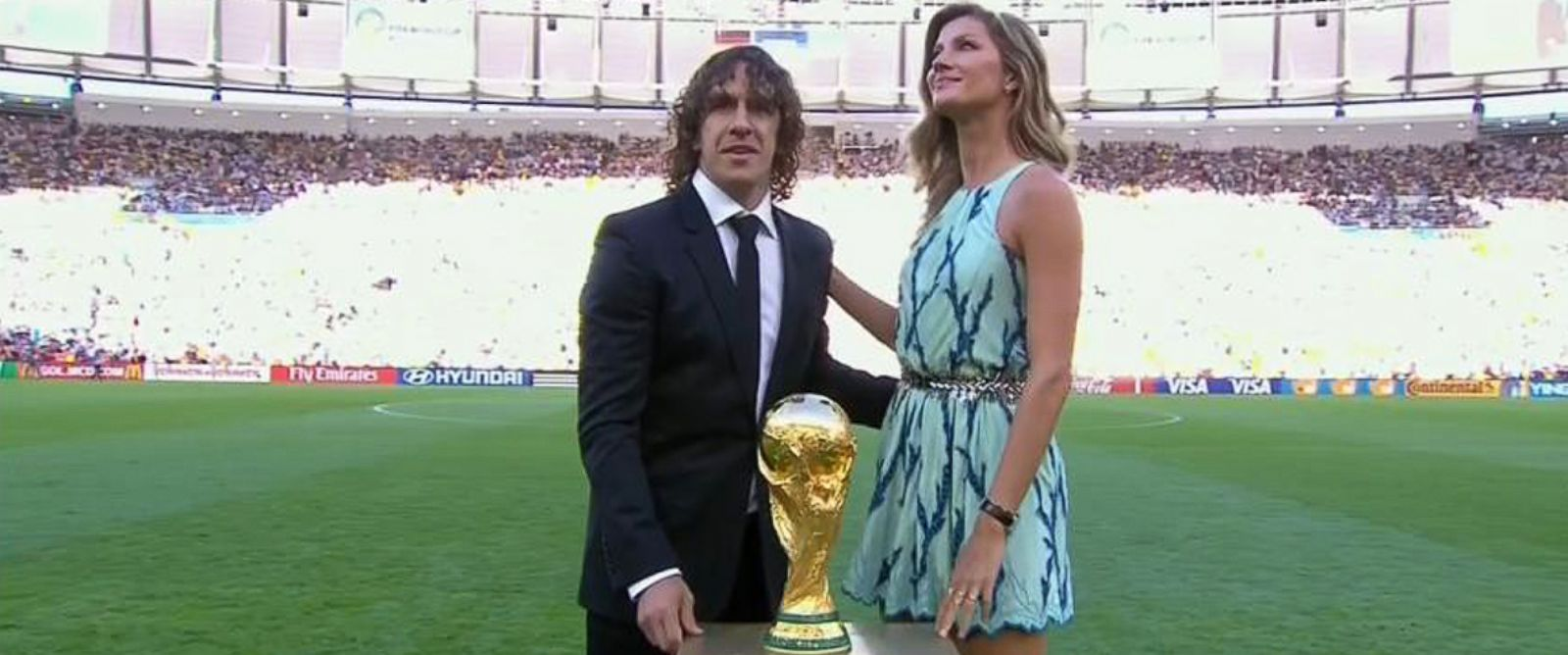 PHOTO: Former Spanish team captain Carles Puyol of Spain and model Gisele Bundchen pose with the World Cup trophy prior to the World Cup final soccer match between Germany and Argentina at the Maracana Stadium in Rio de Janeiro, July 13, 2014.