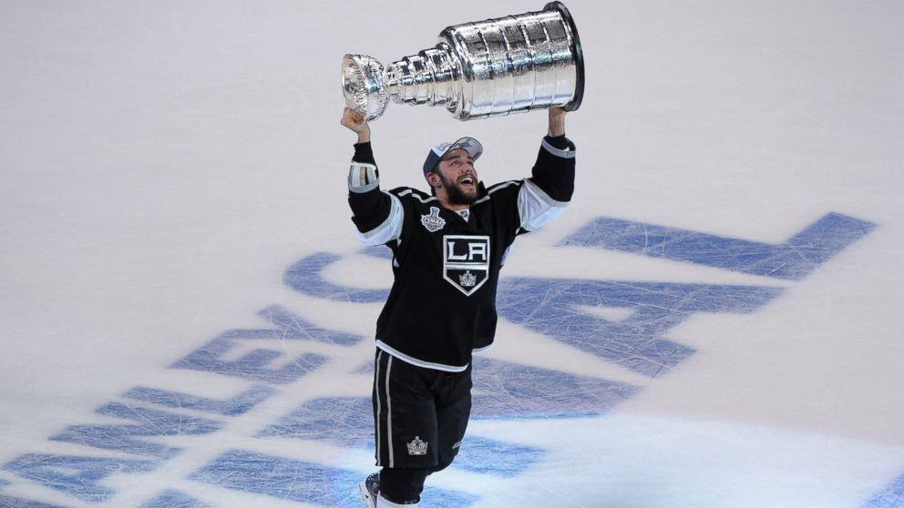 PHOTO: Los Angeles Kings defenseman Alec Martinez carries the Stanley Cup after beating the New York Rangers in Game 5 of the NHL Stanley Cup Final series Friday, June 13, 2014, in Los Angeles. The Kings won, 3-2.