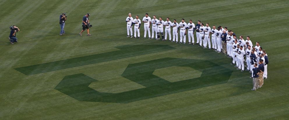 PHOTO: San Diego Padres players stand in right field observing 19 seconds of silence in honor of Hall of Fame player Tony Gwynn during ceremonies prior to a baseball game against the Seattle Mariners, June 18, 2014, in San Diego.