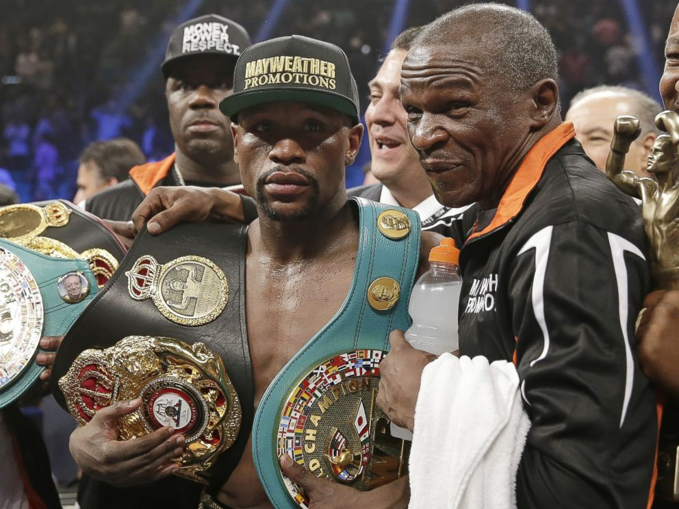 PHOTO: Floyd Mayweather Jr., left, poses with his champions belts and his father, head trainer Floyd Mayweather Sr., after his victory over Manny Pacquiao, from the Philippines, in their welterweight title fight on Saturday, May 2, 2015 in Las Vegas.