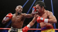 PHOTO: Floyd Mayweather Jr., left, hits Manny Pacquiao, from the Philippines, during their welterweight title fight on Saturday, May 2, 2015 in Las Vegas.