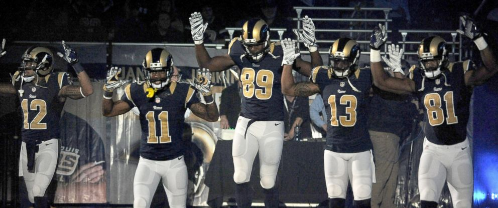 PHOTO: Members of the St. Louis Rams raise their arms in awareness of the events in Ferguson, Mo., as they walk onto the field during introductions before an NFL football game against the Oakland Raiders, Nov. 30, 2014, in St. Louis.