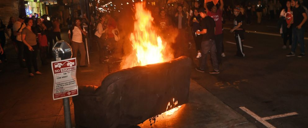 San Francisco Giants fans walk past a couch on fire in the Mission district after the San Francisco Giants beat the Kansas City Royals to win the World Series on Wednesday, Oct. 29, 2014, in San Francisco.