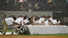 PHOTO: Grounds crew members unroll the tarp during a rainstorm in the fifth inning of a baseball game between the Texas Rangers and the New York Yankees at Yankee Stadium in New York, July 23, 2014.
