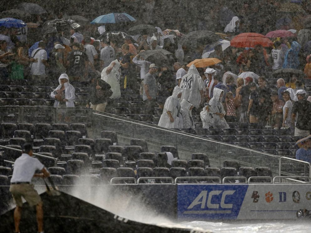 PHOTO: Fans scramble for cover as a rainstorm interrupts the fifth inning of a baseball game between the Texas Rangers and the New York Yankees at Yankee Stadium in New York, July 23, 2014.