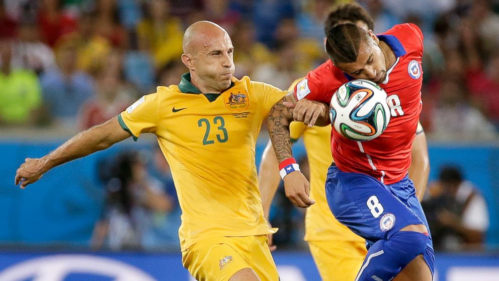 PHOTO: Australias Mark Bresciano, left, and Chiles Arturo Vidal battle for the ball during the group B World Cup soccer match between Chile and Australia at the Arena Pantanal in Cuiaba, Brazil, June 13, 2014.