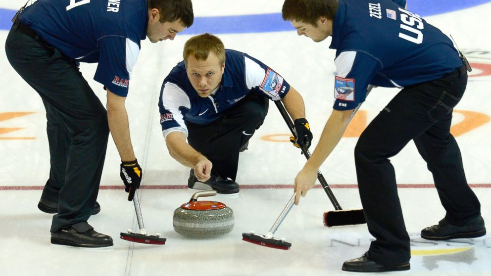 PHOTO: John Landsteiner of USA (L) and team mate Jared Zezel (R) sweep after Jeff Isaacson throws a rock during the Olympic Qualification Tournament tie-breaker match between USA and Korea, Dec. 14, 2013 in Fussen, Germany.
