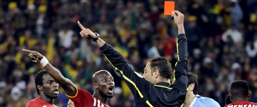 PHOTO: Portuguese referee Olegario Benquerenca hands a red card to Uruguays striker Luis Suarez (unseen) during the 2010 World Cup quarter-final football match Uruguay vs. Ghana, July 2, 2010, in Johannesburg.