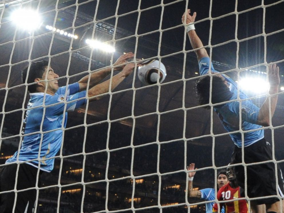 PHOTO: Uruguays striker Luis Suarez, left, stops the ball with his hand during the 2010 World Cup in Soweto, South Africa.