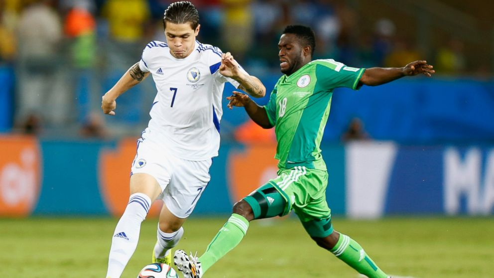 PHOTO: Muhamed Besic of Bosnia and Herzegovina is challenged by Michael Babatunde of Nigeria during the 2014 FIFA World Cup Group F match between Nigeria and Bosnia-Herzegovina at Arena Pantanal on June 21, 2014 in Cuiaba, Brazil.