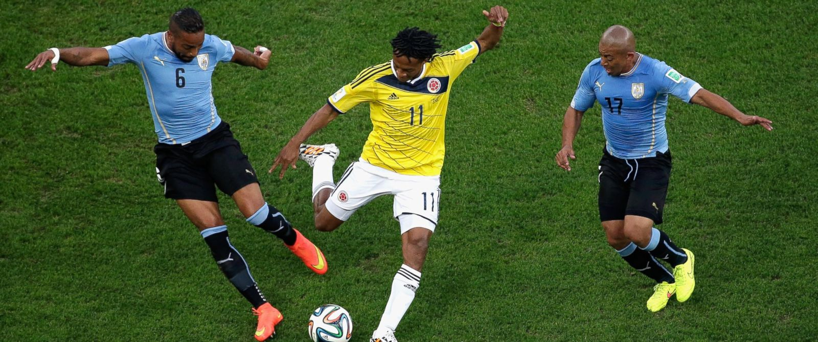 PHOTO: Alvaro Pereira of Uruguay challenges Juan Guillermo Cuadrado of Colombia during the 2014 FIFA World Cup Brazil round of 16 match between Colombia and Uruguay at Maracana on June 28, 2014 in Rio de Janeiro, Brazil.