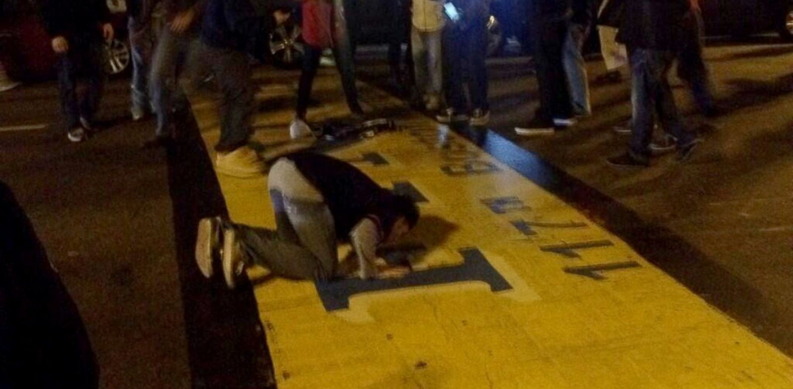 PHOTO: Fans cheered and kissed the Boston Marathon finish line after the Red Sox won the World Series, Oct. 30, 2013, in Boston.