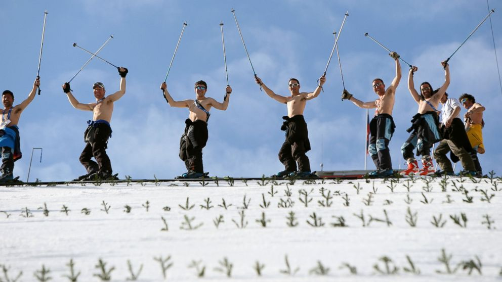 PHOTO:Course workers take off their shirts to enjoy the warm weather as they prepare the landing hill before the mens Nordic combined normal hill training jump at the RusSki Gor