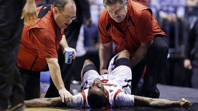 PHOTO: Trainers check on Louisville guard Kevin Ware (5) after Ware injured his lower right leg during the first half of the Midwest Regional final against Duke in the NCAA college basketball tournament, Sunday, March 31, 2013, in Indianapolis