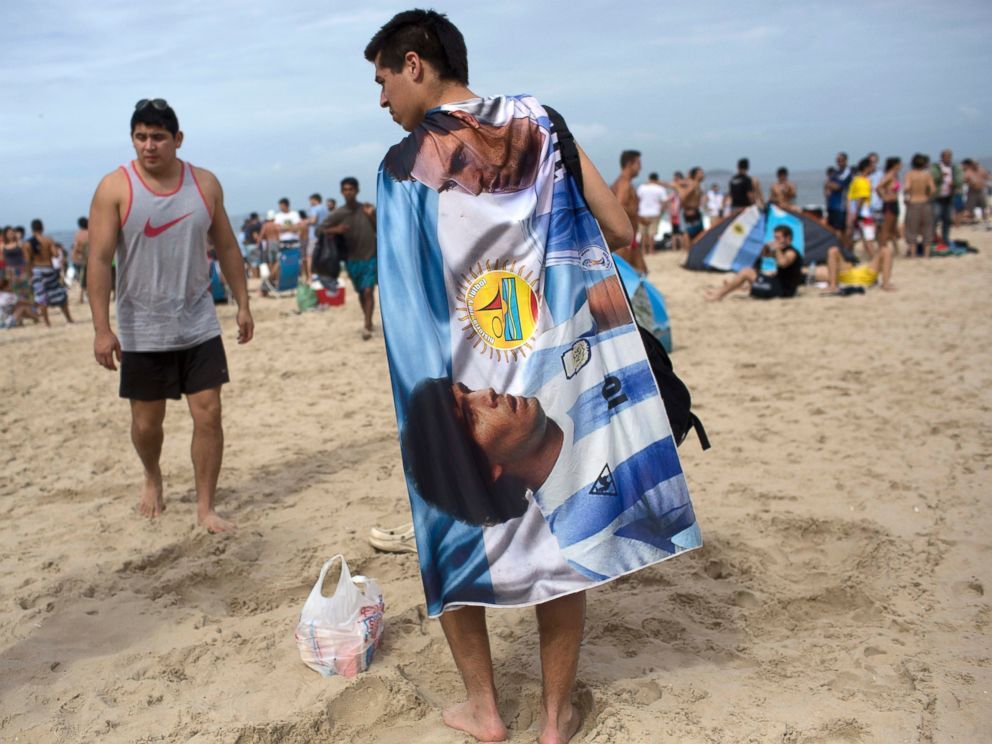 PHOTO: A soccer fan wears a banner designed with images of Diego Maradona and Lionel Messi, on Copacabana Beach in Rio de Janeiro, Brazil, July 12, 2014.