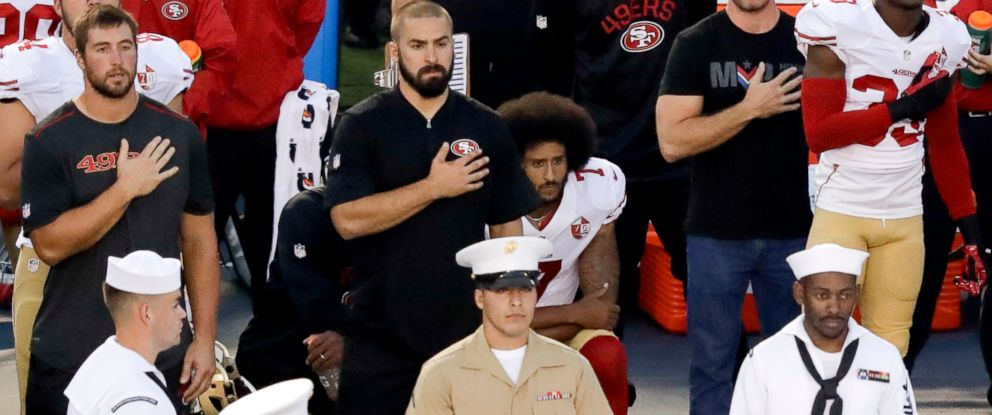 PHOTO: San Francisco 49ers quarterback Colin Kaepernick, middle, sits during the national anthem before the teams NFL preseason football game against the San Diego Chargers, Sept. 1, 2016, in San Diego.