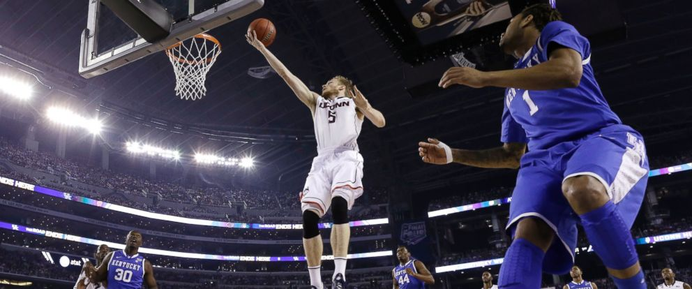PHOTO: Connecticut guard Niels Giffey (5) drives to the basket in front of Kentucky guard James Young, right, during the first half of the NCAA Final Four tournament college basketball championship game Monday, April 7, 2014, in Arlington, Texas.