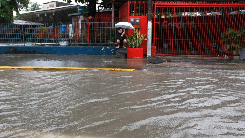 PHOTO: A man takes cover from the rain on the side of a flooded street in Recife, Brazil, June 26, 2014.