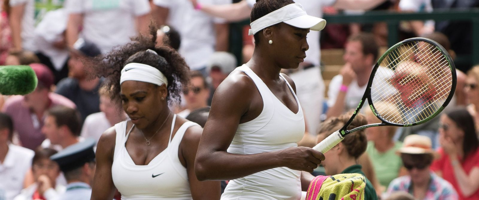 PHOTO: Serena and Venus Williams pass on the changeover during their match at the Wimbledon Championships in London, July 6, 2015.
