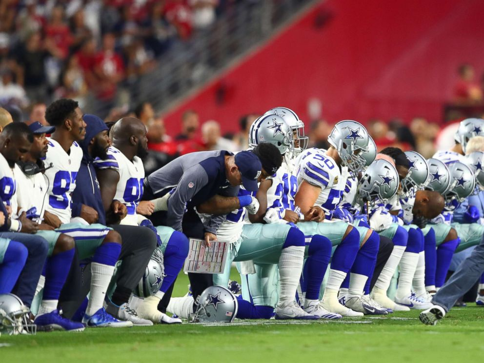 PHOTO: Dallas Cowboys players kneel together with their arms locked prior to the game against the Arizona Cardinals at University of Phoenix Stadium, Sept. 25, 2017.