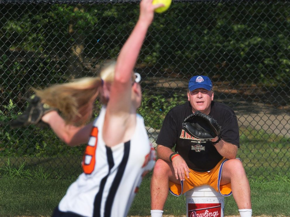 PHOTO: Curt Schilling, coach of the Drifters, a 16-and-under girls softball team, catches his daughter Gabby at Shonda Schilling Field in Medfield, Ma. on July 19, 2013.