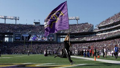 PHOTO: A Baltimore Ravens cheerleader carries the teams flag on the field before the start of the Ravens game against the Oakland Raiders at M&T Bank Stadium, Nov. 11, 2012, in Baltimore.