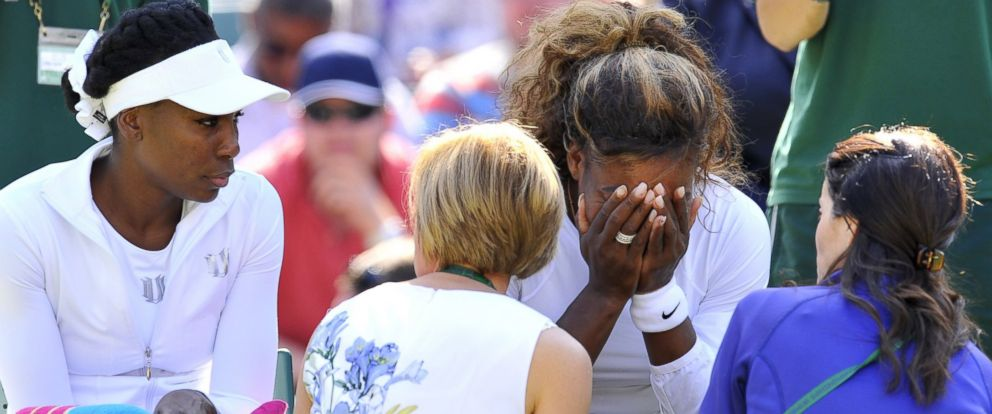 PHOTO: Serena Williams sits with her hands on her face next to her sister Venus Williams as Serena was taken ill during their womens doubles second round match during the 2014 Wimbledon Championships in Wimbledon, southwest London, on July 1, 2014.