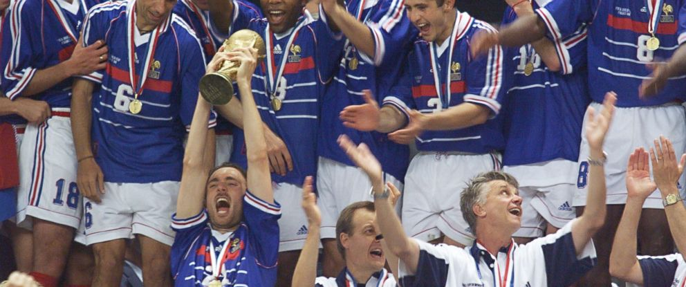 PHOTO: French forward Christophe Dugarry holds the FIFA trophy as the French team celebrates their victory over Brazil on July 12, 1998 at the Stade de France in Saint-Denis.