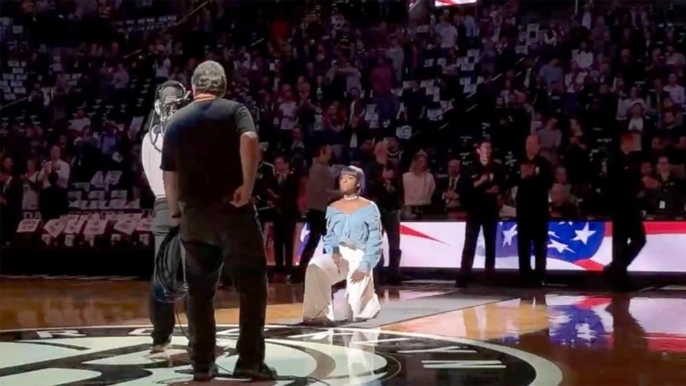 Singer Justine Skye takes a knee while performing national anthem during Brooklyn Nets home opener