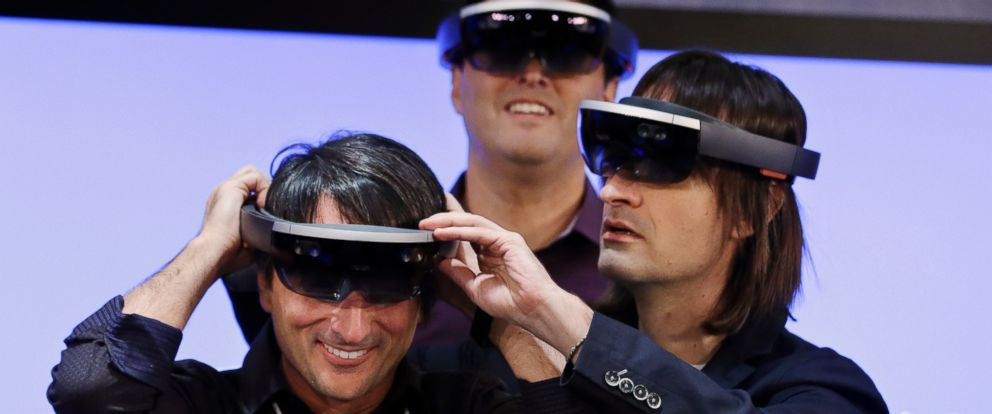 """PHOTO: Microsofts Joe Belfiore (L) smiles as he tries on a """"Hololens"""" device with colleagues Alex Kipman (R) and Terry Myerson following an event demonstrating new features of Windows 10 at the companys headquarters on Jan. 21, 2015, in Redmond, Wash."""