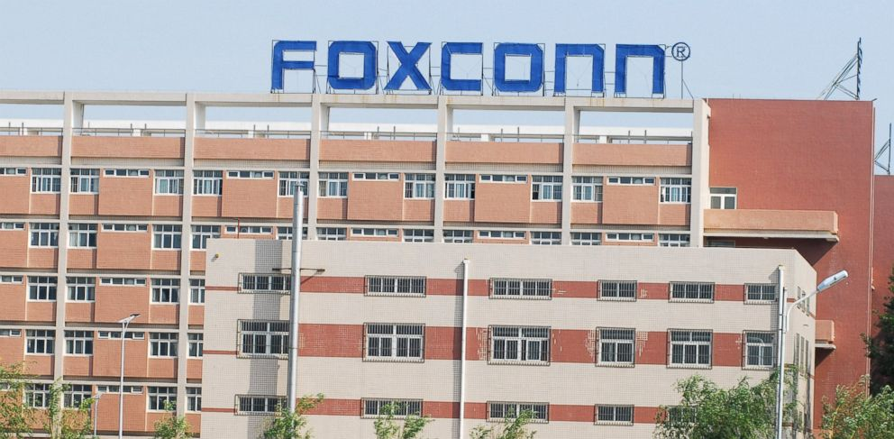 PHOTO: Chinese Foxconn employees walk across a bridge in front of the Foxconn Yantai plant
