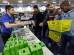 PHOTO: Nikolai Vacca, left, explains Xbox One accessories to customers at a Best Buy store.
