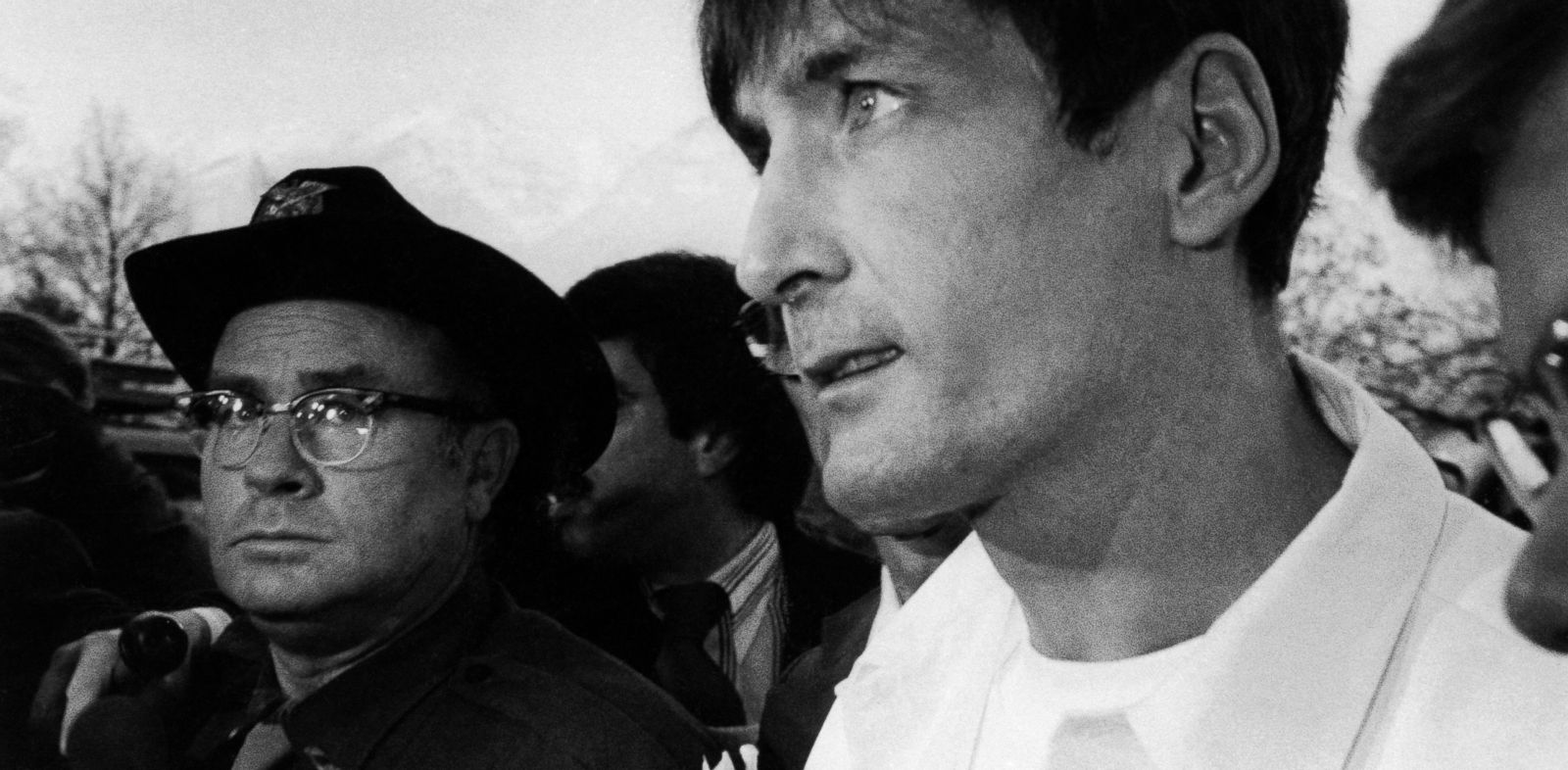 PHOTO: Gary Gilmore, wearing prison maximum security white uniform, faces barrage of newsmen and law enforcement officers on way to 4th District Court for new execution date in Provo, Utah, Dec. 3, 1976.