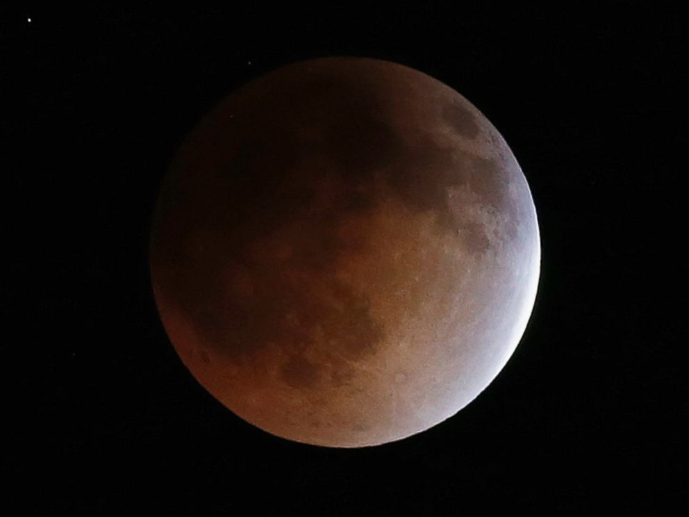 PHOTO: The moon turns an orange hue during a total lunar eclipse in the sky above Phoenix
