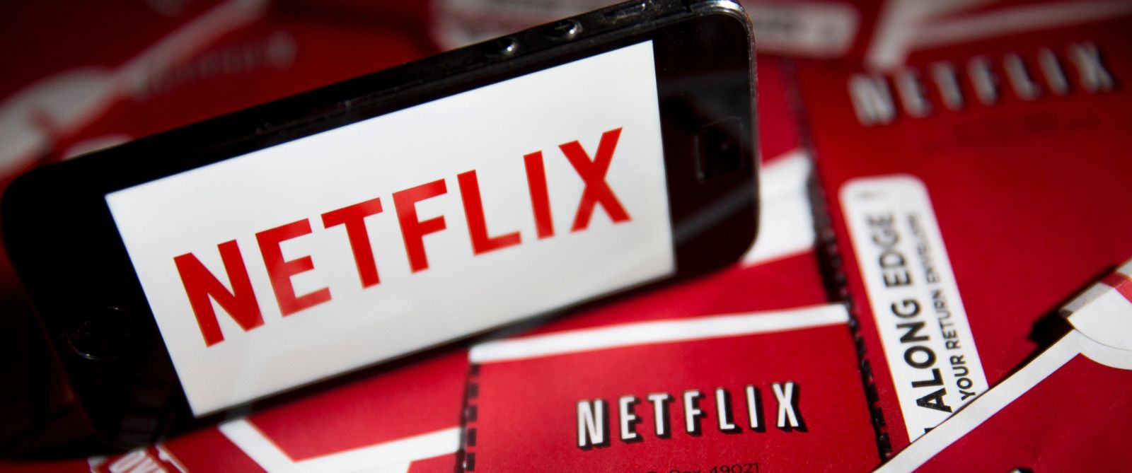 PHOTO: The Netflix Inc. logo is displayed on an Apple Inc. iPhone 5s surrounded by DVD mailers in this arranged photograph in Washington on April 14, 2015.