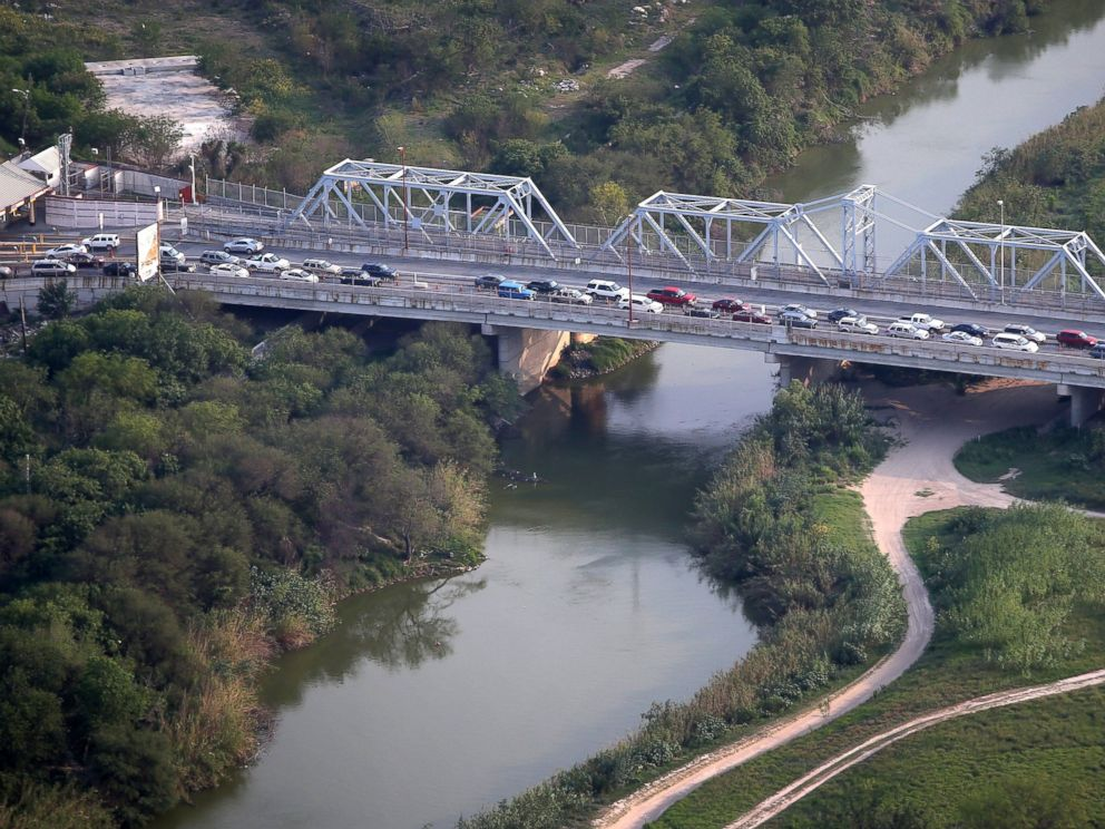 PHOTO: Cars drive from Matomoros, Mexico (L), across the U.S.-Mexico border at the Rio Grande, May 21, 2013, into Brownsville, Texas.