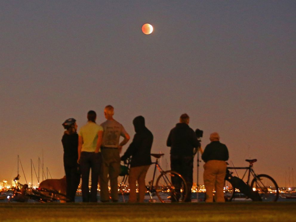 PHOTO: People watch as the Blood Moon rises over the water in Wlliamstown in Melbourne, Australia