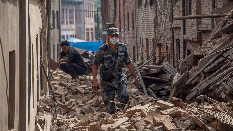 PHOTO: A member of police forces walk down a street covered in debris after buildings collapsed, April 26, 2015, in Bhaktapur, Nepal.
