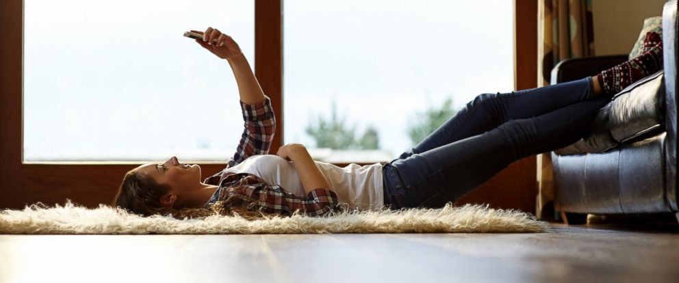 PHOTO: Woman lounges around using mobile phone.