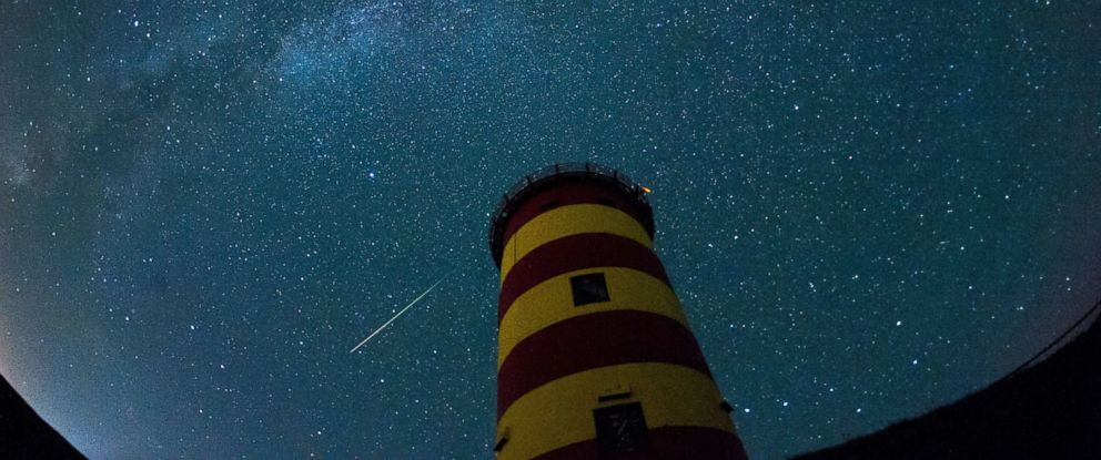 PHOTO: A falling star crosses the night sky behind a lighthouse is pictured during the peak in activity of the annual Perseids meteor shower on Aug. 13, 2015 in Pilsum, Germany.