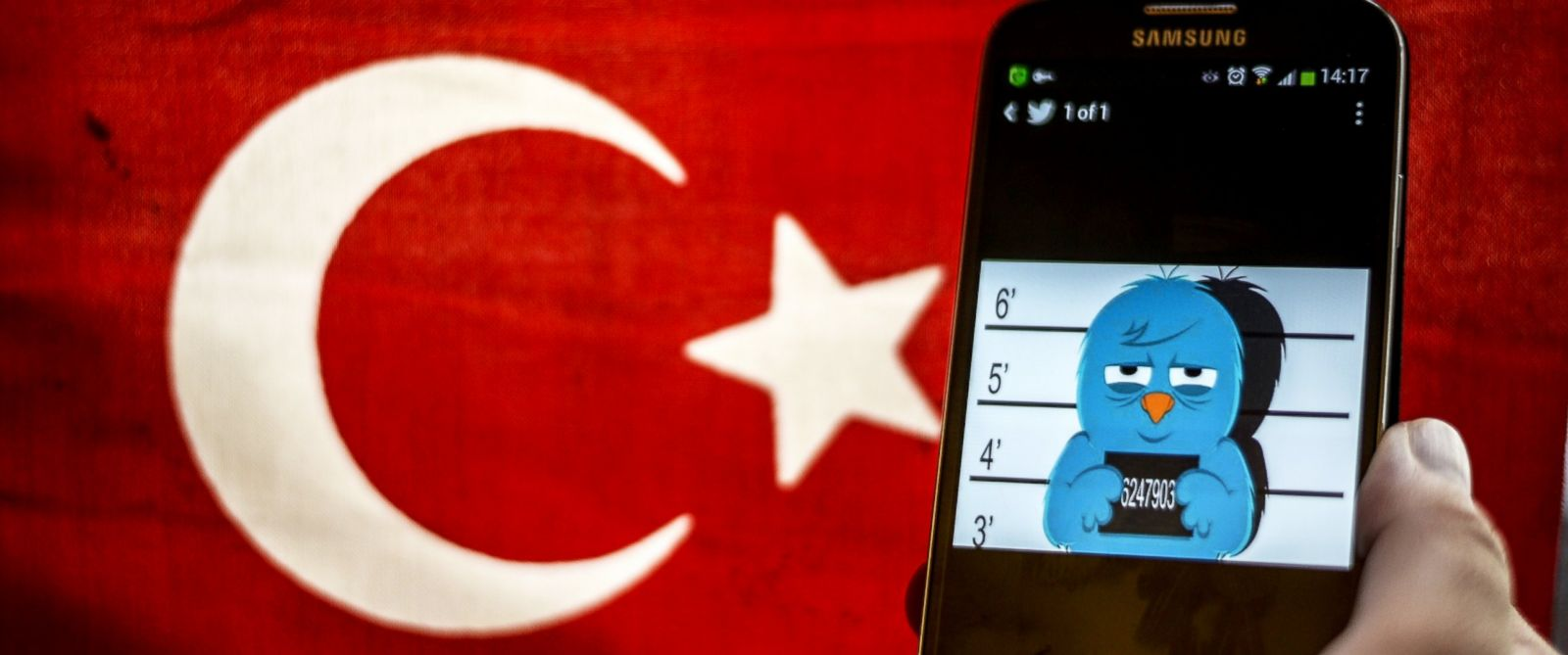 PHOTO: A picture representing a mugshot of the twitter bird is seen on a smart phone with a Turkish flag, March 26, 2014, in Istanbul.