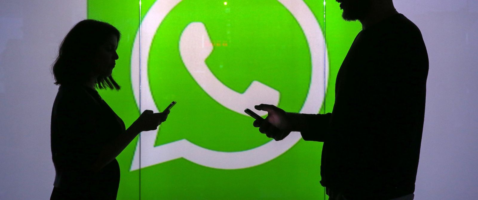 PHOTO:People are seen as silhouettes as they check mobile devices while standing against an illuminated wall bearing WhatsApp Incs logo in this arranged photograph in London, Jan. 5, 2016.